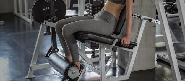 無駄のない体と体のスリムな形状の建物の重量挙げを持つトレーニング女性。