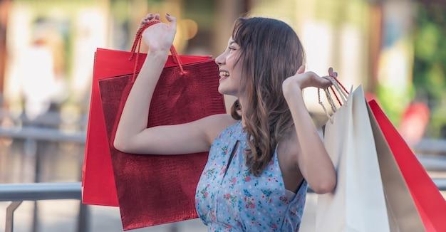 楽しんで買い物袋を持って幸せな若い女。