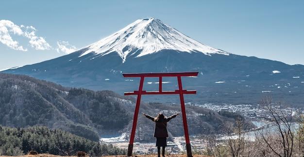 幸せな旅行者の女性は背景に富士山で頭の上に腕を表示します。