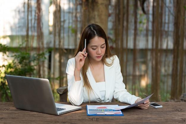 Коммерсантка сидя на таблице с ручкой и думая пока работающ на бумажном листе около компьтер-книжки