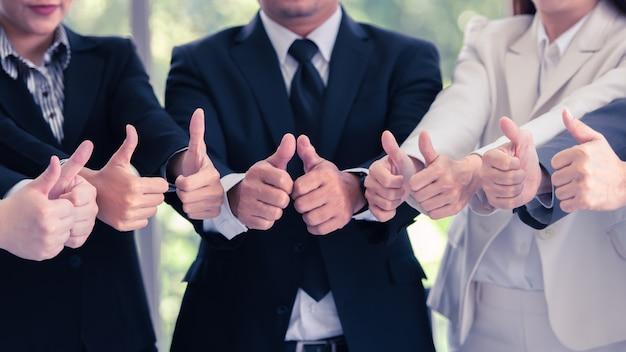 ビジネスマンのチームワークが親指を立て、それを可能にする表現、素晴らしい仕事、戦い続けます。