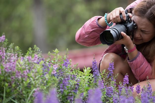 女性が公園で花を取ってデジタル一眼レフカメラを使用して。