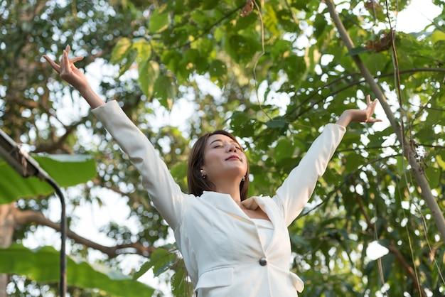 Бизнес женщина поднял руки вверх от счастья и освежающий в прекрасный день.