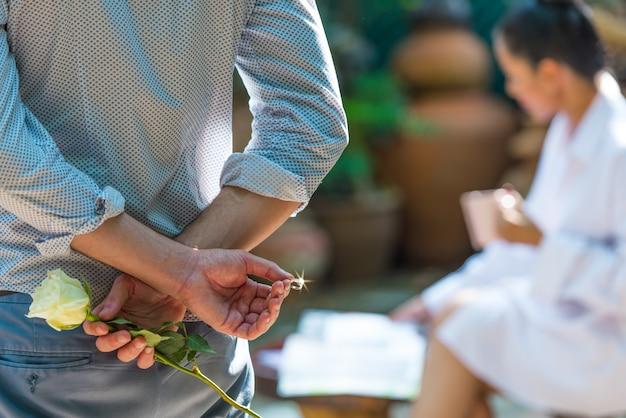 結婚の提案をするための彼の背中の後ろに白いバラと結婚指輪を持って男。