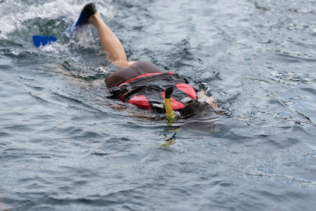 シュノーケルとスキューバシューズ(ドライブスリッパ、ダイビングシューズ)を着てプールで水中を泳いでいる若い女性。