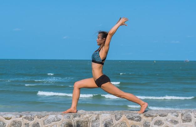 若い女性がビーチで自然に朝のヨガを練習します。