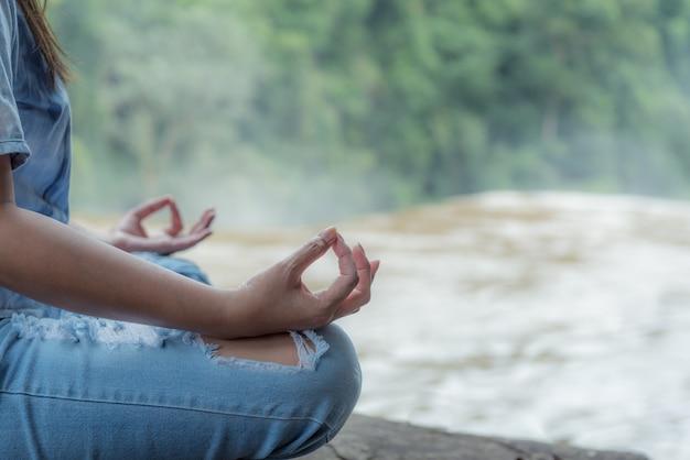 滝で瞑想をしている若いヨガ女性。
