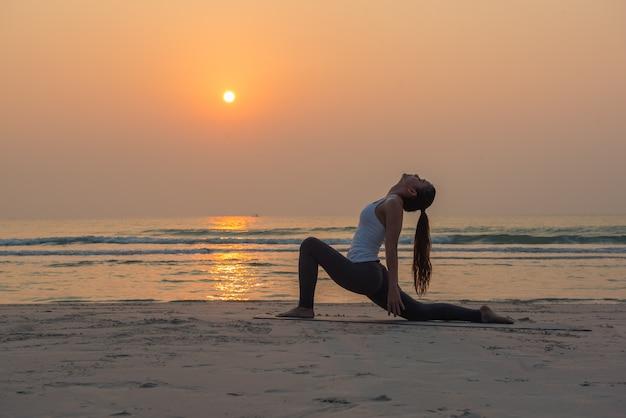 日の出ビーチでヨガのポーズを練習する若い健康的なヨガ女性