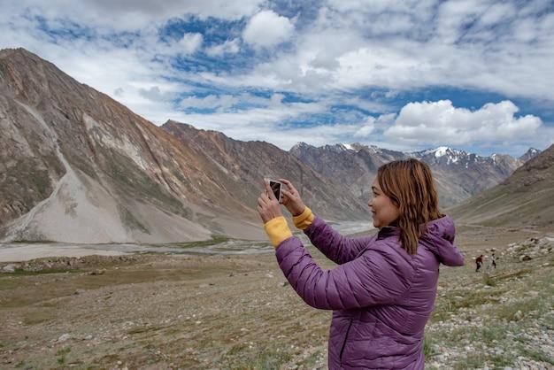 Туристический рукой, держащей мобильный телефон, фотографируя пейзаж в выходные