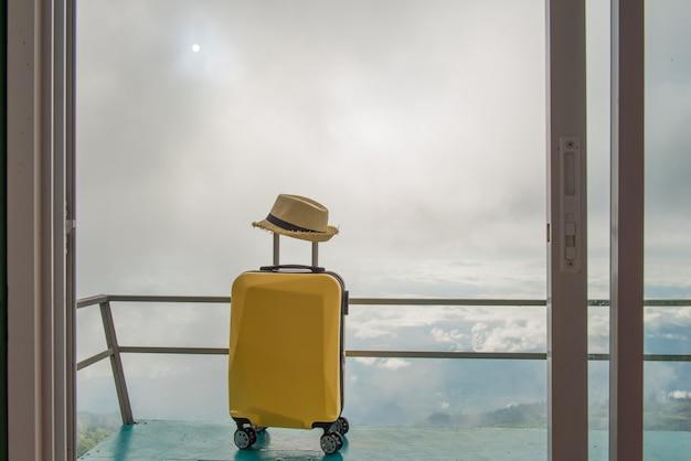 美しい風景のホテルや宿泊施設での旅行用バッグや旅行用スーツケースと帽子