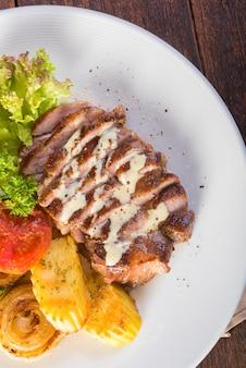 Стейк из свинины на гриле, запеченный картофель и овощной салат на деревянный стол.