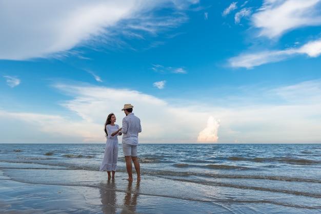 幸せな若いカップルお互いを保持していると夏のビーチで一緒に楽しんで笑っています。
