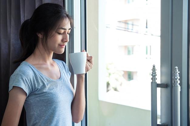 寝室のドアでのコーヒーのカップを持つアジアの女性の肖像画