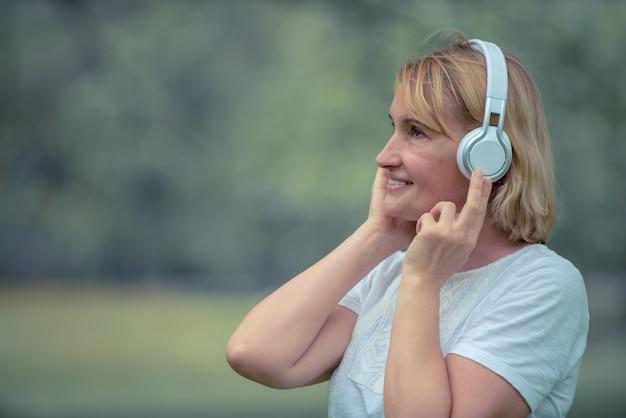 Музыка счастливой пожилой женщины слушая на наушниках в парке
