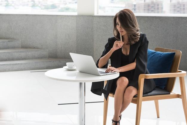 Женщина работника офиса думая сидя на ручке удерживания стола и используя портативный компьютер.