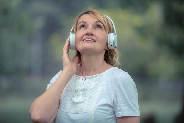 年配の幸せな女がスマートフォンで音楽を聴きます。