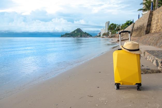 Чемодан с шляпой на пляже с небом облаков голубым, путешествуя концепция.