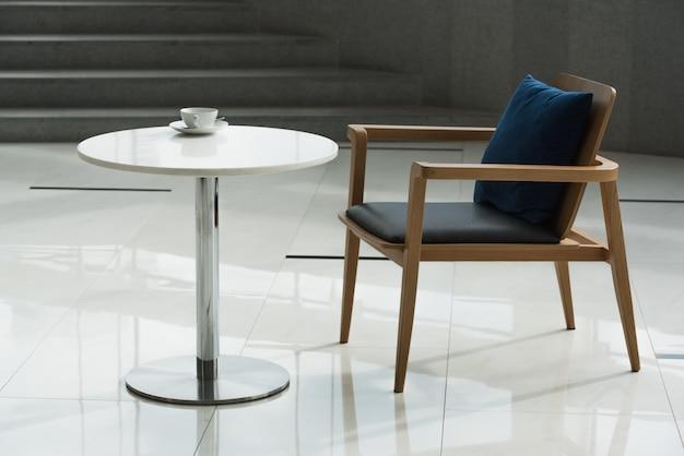 空のモダンな机と椅子とコーヒーカップ。