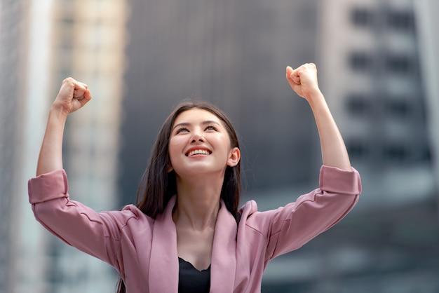 Портрет женщины уверенно бизнес, улыбаясь и поднял руки вверх на фоне города.