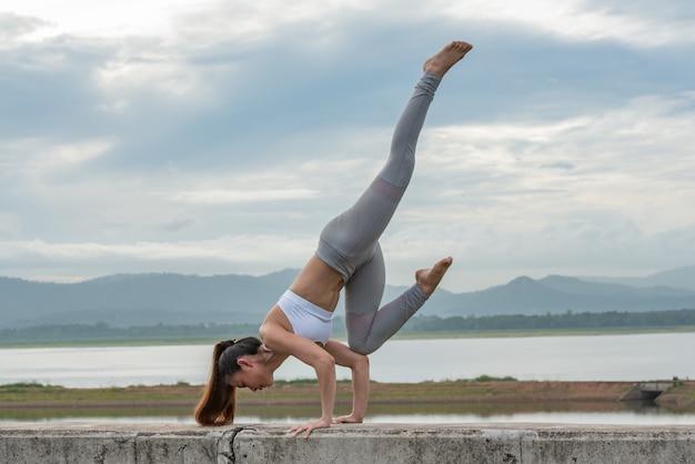 Женщина спорт детенышей делая йогу на озере с предпосылкой горы.