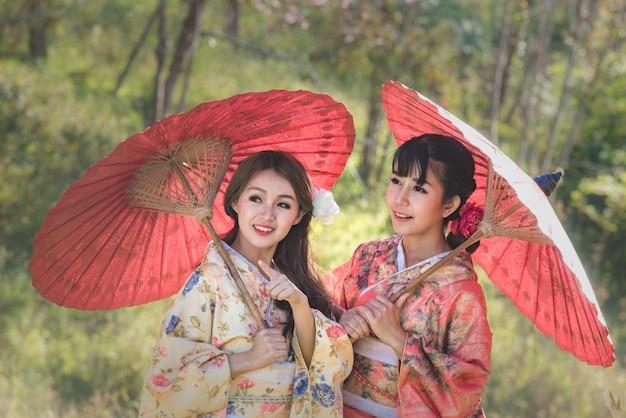 Азиатские молодые женщины нося традиционное японское кимоно держа красный зонтик в парке вишневого цвета.