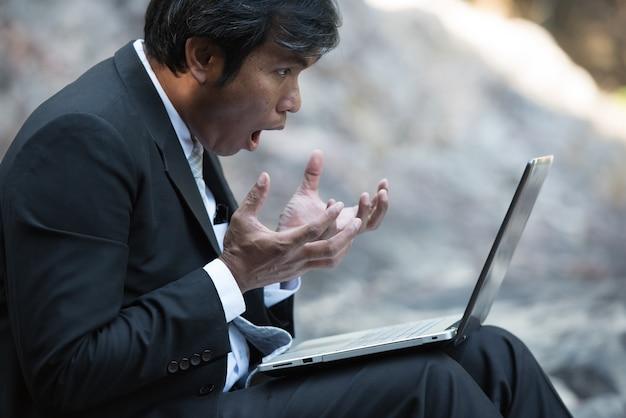 Удивлен бизнесмен в костюме, глядя на экран ноутбука с возбужденных в парке.