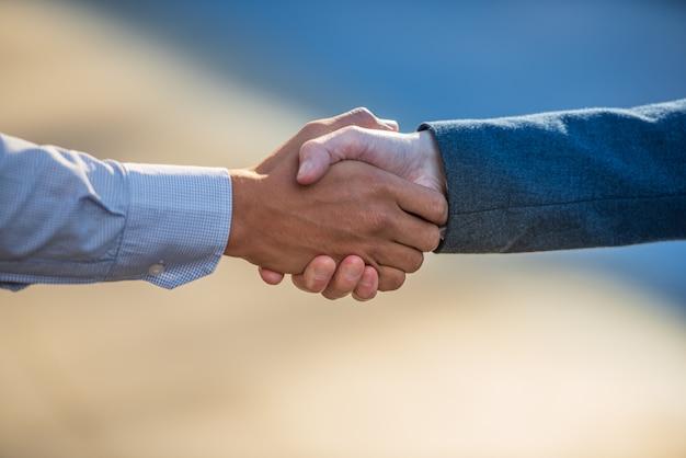 ビジネスの人々は一緒に握手し、チームワークでビジネスをしています。