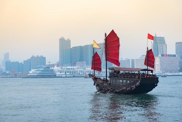 Путешествие по гонконгу, традиционный деревянный парусник плывет по виктории.