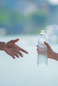 若い女性の手を与えるまたはフィットネス運動後の男に新鮮な冷たい飲料水のボトルを提供します。
