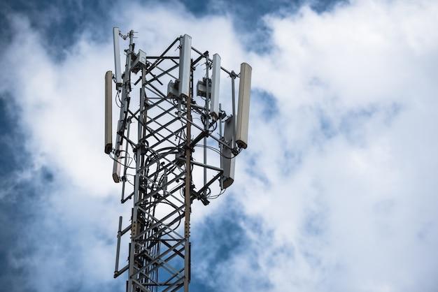 雲を背景に空に携帯電話の塔、携帯電話の塔、電柱などのアンテナを備えた通信塔。