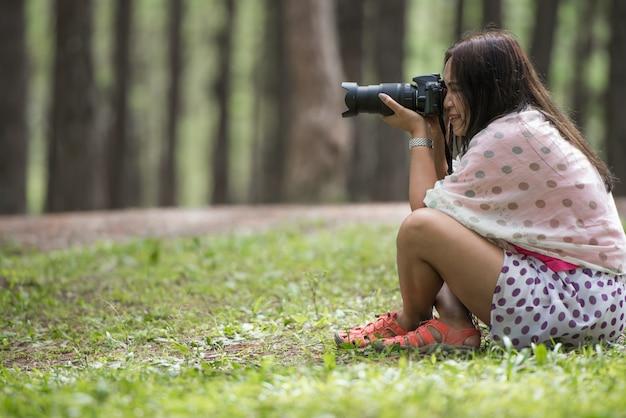 デジタル一眼レフカメラ撮影ポーズを持つ女性