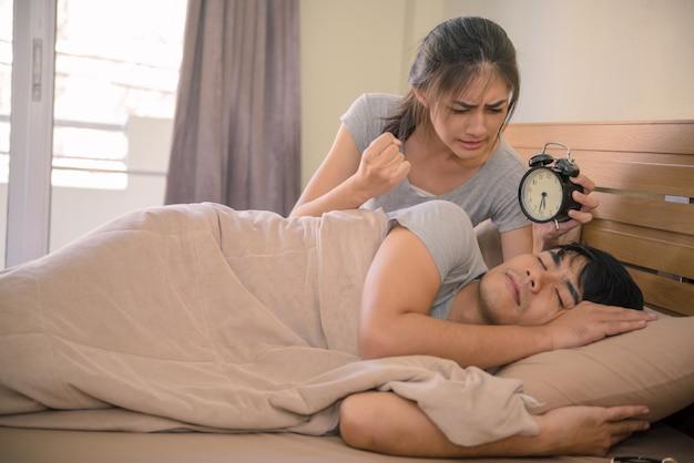 目覚まし時計が目を覚ます彼の妻をベッドの中で若いカップル。
