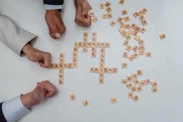 ビジネスの人々のグループは、クロスワードパズルの言葉でチームワークを表現する手を親指します。