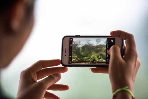 週末に風景の写真を撮りながら携帯電話を持っている観光手、旅行携帯電話のコンセプトで写真を撮る。