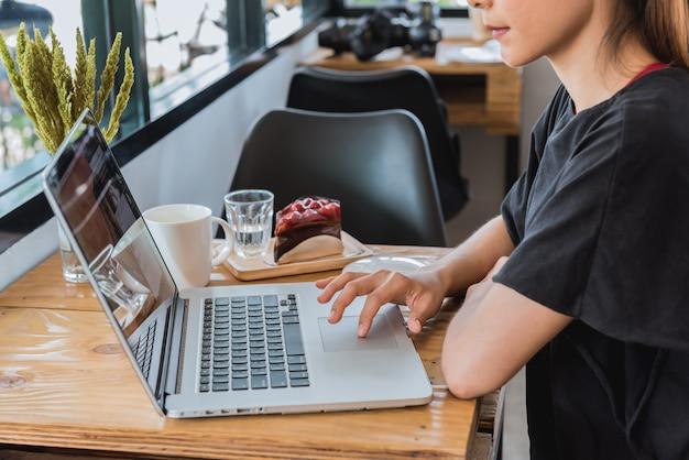 アジアの女性がカフェでラップトップコンピューターに取り組んでいます。