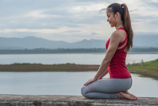 ヨガの女性は運動をする前に瞑想を立地します。