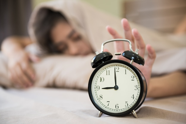 彼女の寝室の目覚まし時計をオフにして、朝目を覚ます幸せな女の子。