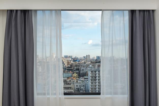 Жалюзи окна с видом на городской пейзаж.
