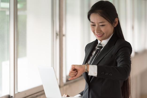 ビジネスの女性が彼女の手を見ています。