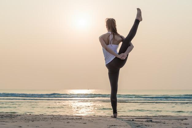 ヨガをやって健康的なヨガ女性は朝のビーチでポーズします。
