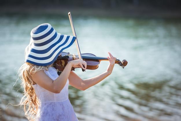アジアの女性が川でバイオリンを弾いています。
