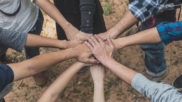 チームワークで手を積み重ねる人々。