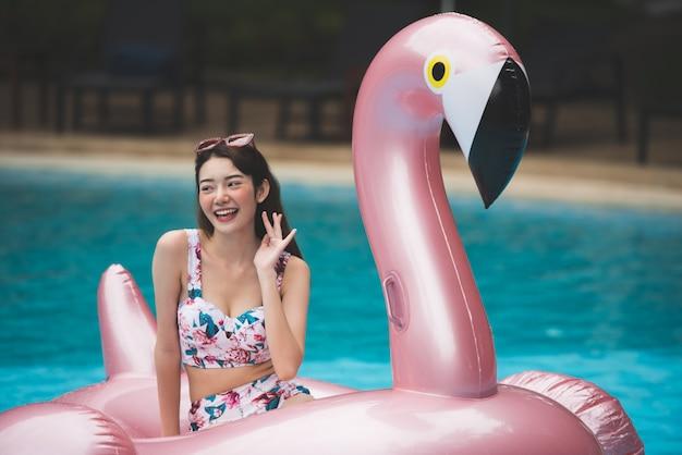 若いアジアの女性は、スイミングプールで巨大なインフレータブルスワンに乗る。