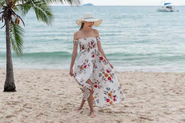 Счастливая молодая азиатская женщина с шляпой идя и ослабляя на пляже песка с счастьем.