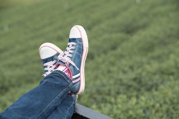 Расслабляющий на зеленом естественном с ногами вверх, близко вверх.