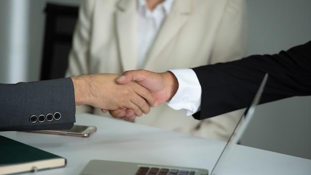 会議で一緒に握手するビジネス人々。