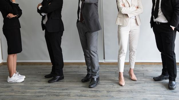 行に立っているさまざまなビジネス人々が足でクローズアップ。