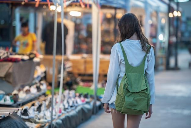 ナイトマーケットで買い物に歩いてバックパックとアジアの若い幸せな女の子。
