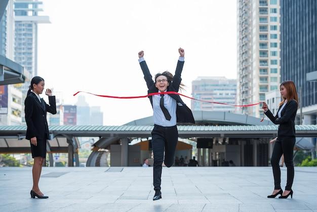 ビジネスの女性は、街の背景、ビジネスコンセプトに勝つためにフィニッシュラインを横切ります。