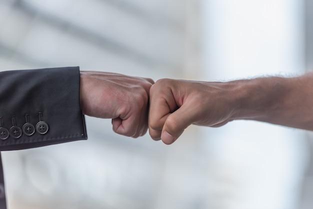 拳を与えるビジネス人々は、オフィスでチームワークで一緒にバンプします。